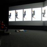 Un miembro del público imita los movimientos de Mia Massimino durante su presentación en vídeo en la Sala de Proyecciones del Museo del Ferrocarril. Crédito de imagen: Mona McKinstry.