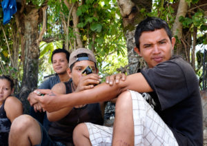 Migrantes se hacen tatuajes mientras esperan el tren en Chiapas, México, cerca de la frontera con Guatemala. Crédito de imagen: Jason De León