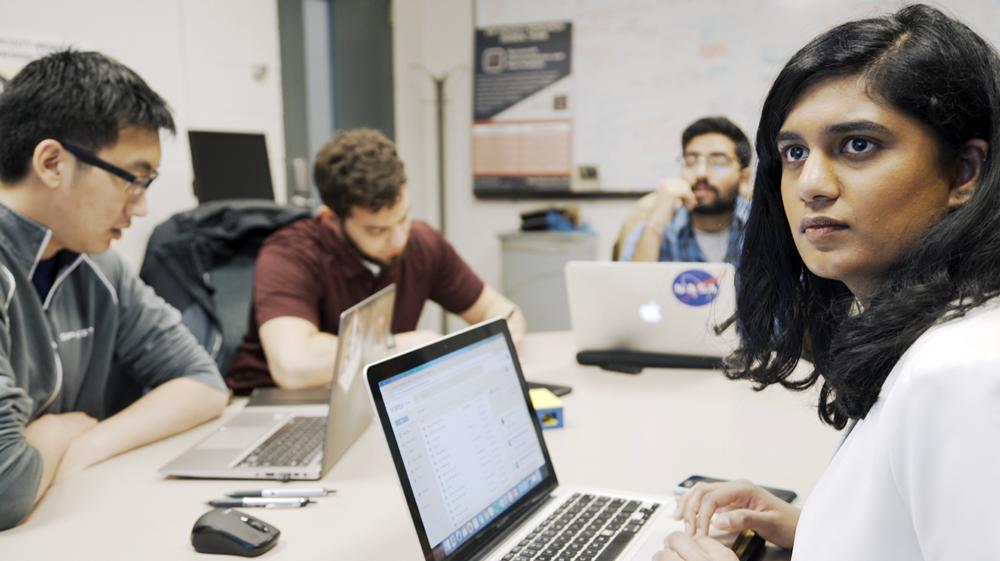 La líder del equipo M-BARC de Universidad de Michigan Hashmita Koka, una estudiante de posgrado en ingeniería aeroespacial, discute la dinámica orbital de la cápsula de tiempo con otros miembros del grupo. Crédito: Robert Coelius