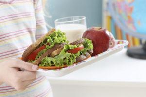 Una bandeja de almuerzo escolar con un sándwich, una gruta y un vaso de leche.