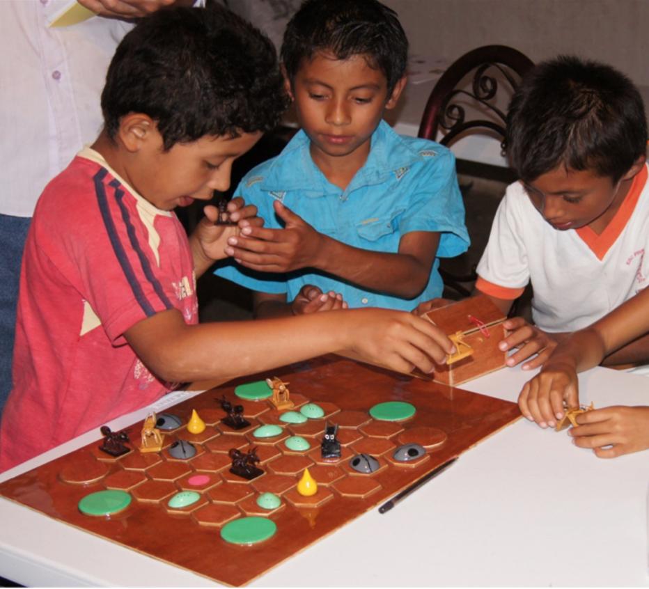 Niños juegan con la versión de lujo de Ajedrez Azteca. Foto cortesía de Luis García Barrios.