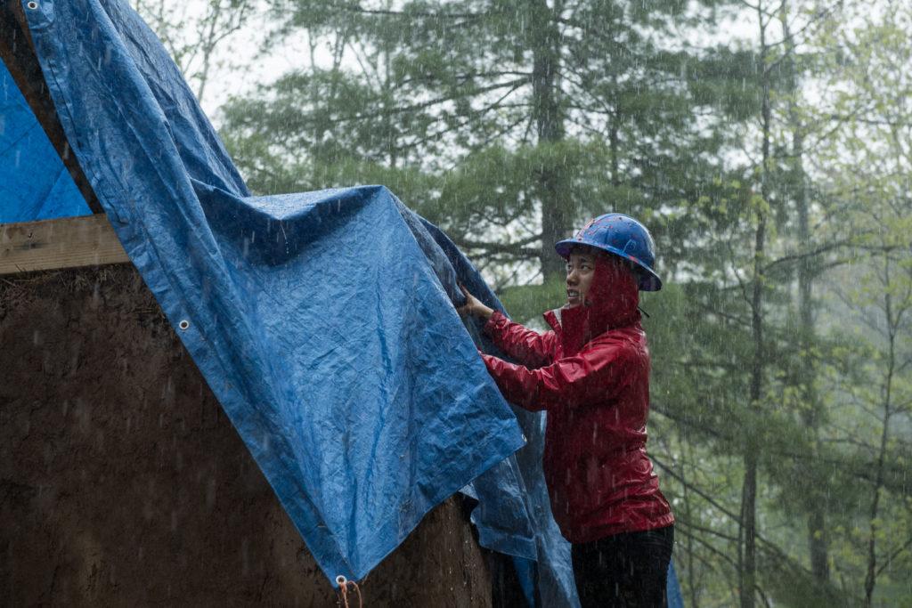 Un estudiante cubre la construcción para proteger la paja de la lluvia.