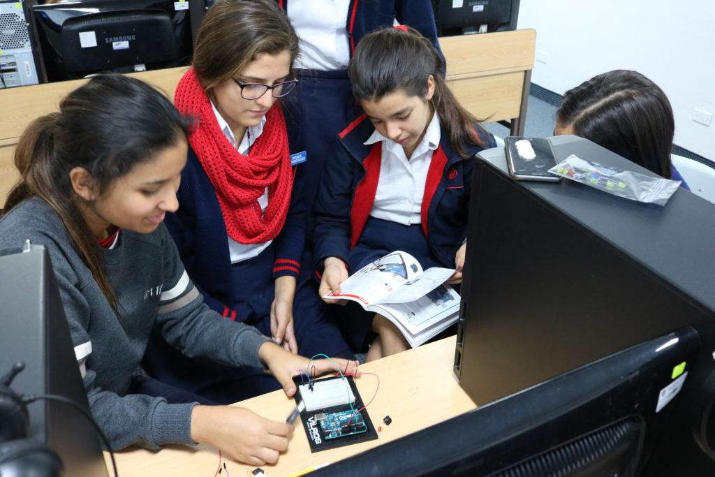La estudiante de Universidad de Michigan Isabella DeShantz trabajando con estudiantes de la secundaria Alpamayo en un proyecto de programación con Python.