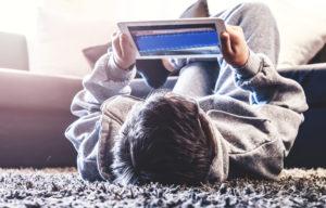 Un joven está tirado en el piso jugando con una tableta