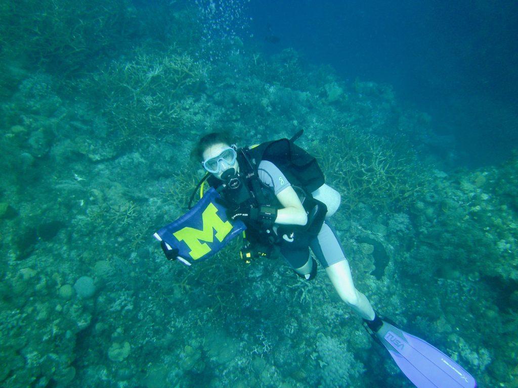 Amy Fraley, una estudiante de posgrado en la Universidad de Michigan, muestra la bandera de la universidad bajo el agua. Fraley trabaja en el laboratorio de David Sherman en el Instituto de Ciencias de la Vida de U-M, cuyo programa ha buscado desde las profundidades del Mar Rojo al campamento base del Monte Everest en el Himalaya nuevos organismos y productos naturales que podrían servir de base para futuros medicamentos.