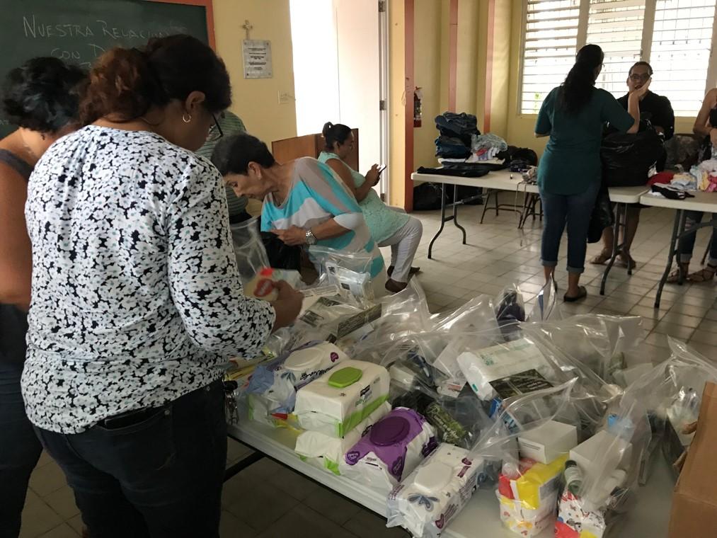 Voluntarios distribuyen paquetes de higiene, almuerzos y ropa mientras otros preparan comida para la comunidad. Foto cortesía de Matos-Moreno.