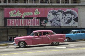 Coches americanos de los años cincuenta en la Habana al frente de un cartel de propaganda del gobierno.