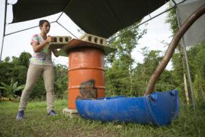 Michelle Farhat, estudiante graduada de maestría en la Escuela de Medio Ambiente y Sostenibilidad de la Universidad de Michigan (SEAS) revisa el gasificador que ella y su equipo construyeron en la Universidad de Puerto Rico Utuado. Crédito de foto: Levi Stroud.