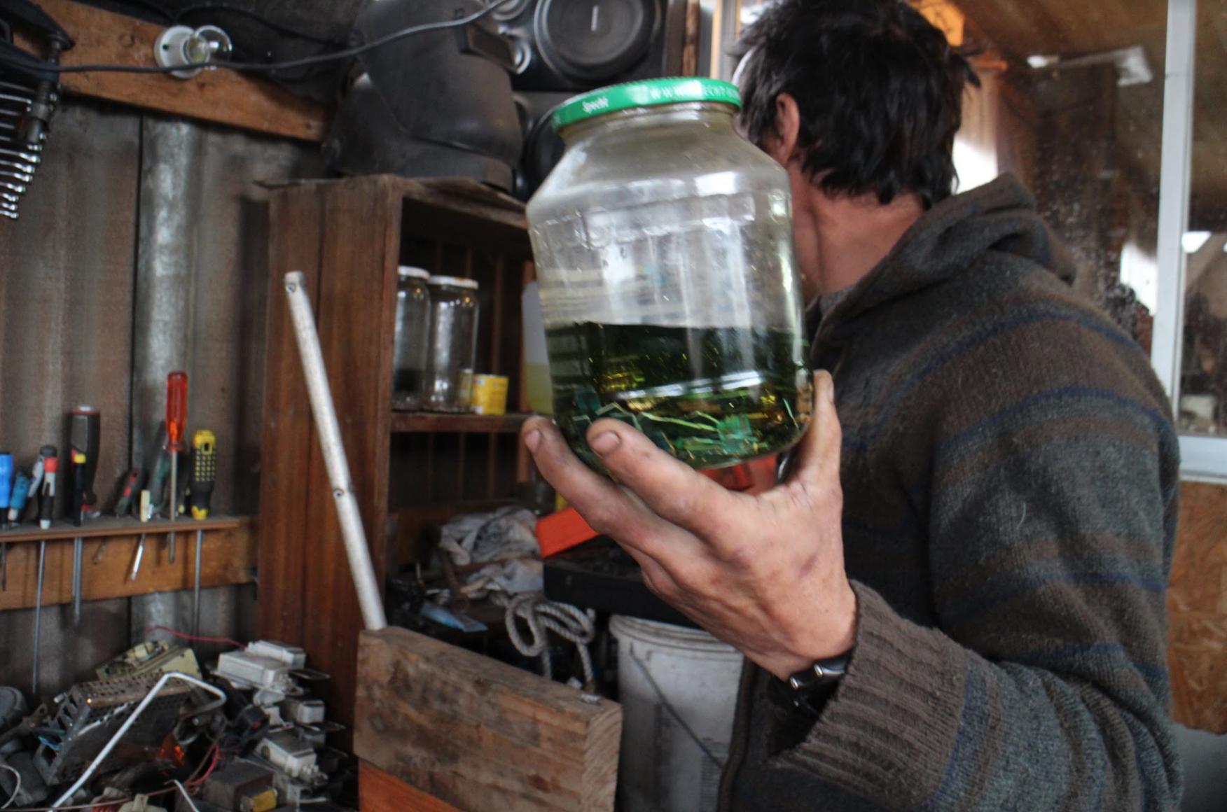 Un reciclador muestra una tarjeta de circuito impreso que ha puesto en ácido para desarmarla. Crédito de imagen: Exposure Research Lab