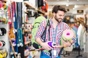 El hombre en la tienda de artículos deportivos compra de artículos para actividades al aire libre. (Imagen)