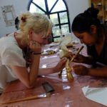 Mia Massimino aprende cómo aplicar pintura de oro en una mano de madera. Crédito de imagen: Mona McKinstry.