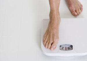 Una mujer se sube a una pesa © Royalty-Free/Corbis