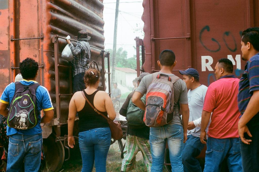 """Migrantes y contrabandistas se reúnen en torno a """"La Bestia"""" después de que el tren se detuvieran en Chiapas, México, cerca de la frontera con Guatemala. Los migrantes deben pagar $100 a los carteles mexicanos en varias paradas a lo largo del camino, haciendo el viaje muy costoso y, a menudo, imposible para ellos. Crédito de imagen: Jason De León."""