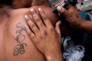 Un joven migrante de Honduras se hace un tatuaje. Con frecuencia, el camino migrante está lleno de horas de espera. Crédito de imagen: Jason De León