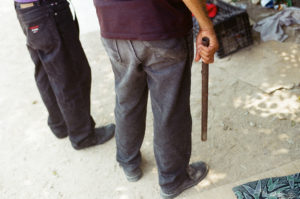 A cuatro millas de distancia, un coyote traficante sostiene una cañería, que en manos adecuadas puede convertirse en un arma. Crédito de imagen: Jason De León.