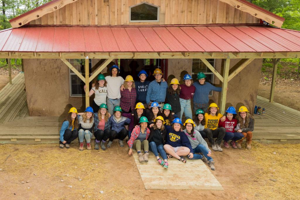 El equipo celebra el haber terminado el edificio de balas de paja