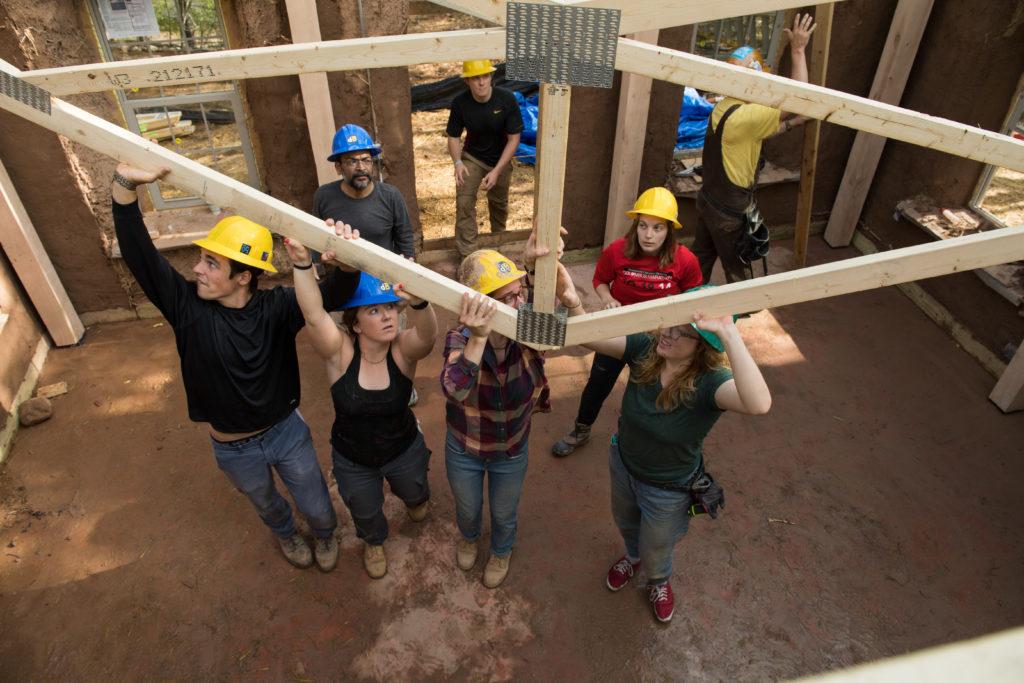 Los estudiantes levantan el techo del edificio de paja.