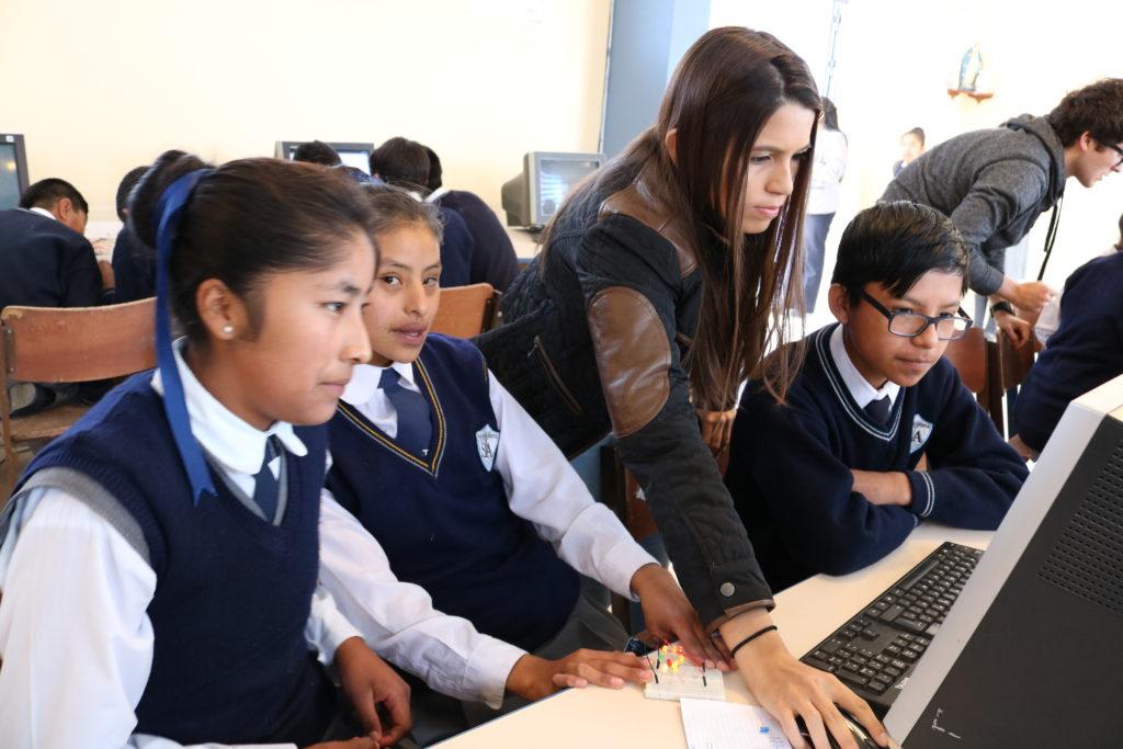 Giuliana Huerta-Mercado, estudiante de la Universidad de Michigan y presidente y fundadora de UTK, ayuda a estudiantes de la secundaria San Juan Apostol en Arequipa, Perú, cargando programas con el software Arduino.