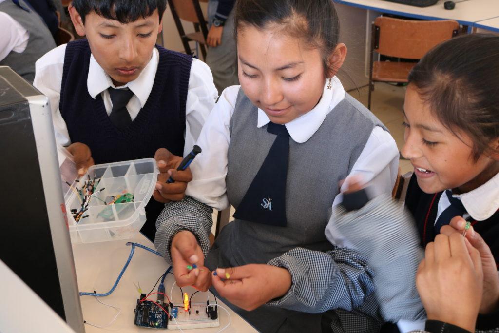 Estudiante trabaja con Arduinos para crear un sistema de iluminación automatizado en la secundaria Villa Caritas en Lima, Perú.