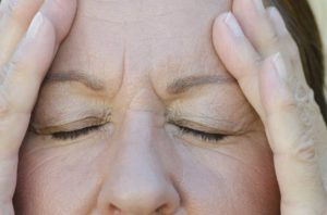 Mujer se toma la cabeza aparentemente sufriendo de dolor de cabeza.