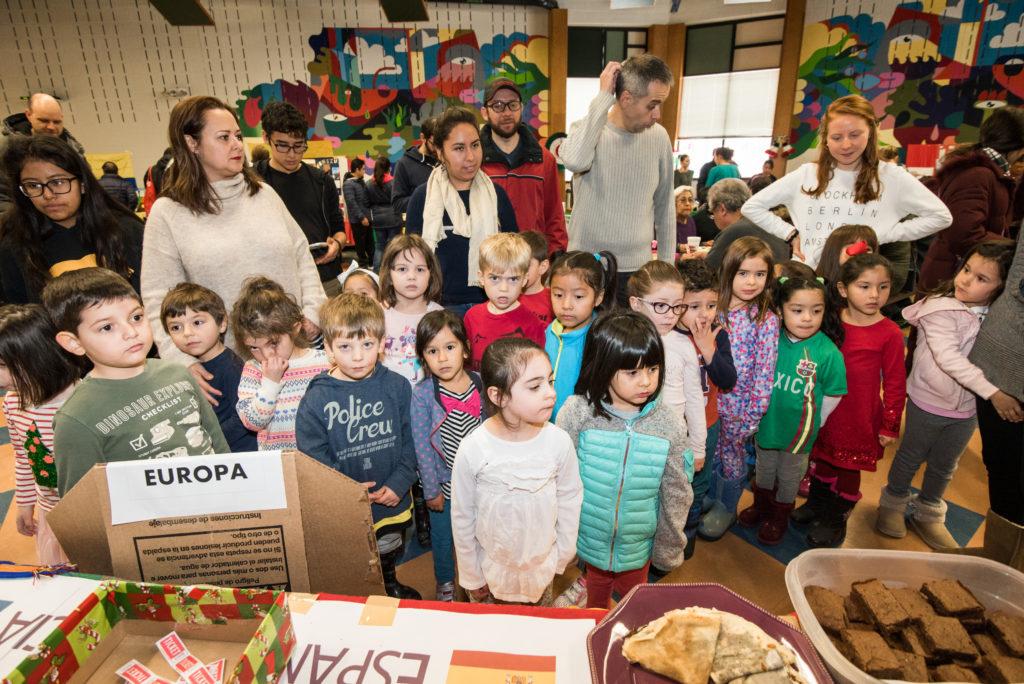 Estudiantes de En Nuestra Lengua pasan por las diferentes mesas en Bach Elementary durante la recaudación annual de fondos para el programa, que incluye la venta de comidas típicas de países de habla hispana.