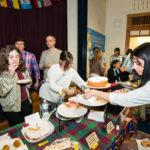 Estudiantes de En Nuestra Lengua pasan por las diferentes mesas en Bach Elementary durante la recaudación anual de fondos para el programa, que incluye la venta de comidas típicas de países de habla hispana en Bach Elementary School. Peter Matthews, Michigan Photography.