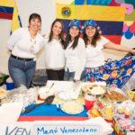 Padres y miembros de la comunidad participant en la recaudación annual de fondos para el programa En Nuestra Lengua, que incluye la venta de comidas típicas de países de habla hispana preparada por los mismos padres.