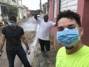 El mejor amigo de Amilcar Matos-Moreno, Alfonso, y Rubén, un voluntario de la comunidad trabajan para limpiar un barrio en Toa Baja, una ciudad que recibió más de seis pies de agua durante Huracán María. Foto cortesía de Matos-Moreno.
