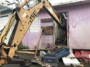 Voluntarios usan una excavadora para limpiar una casa abandonada que, debido a su proximidad con otras casas, se había convertido en la fuente de la plaga de mosquitos y ratas para el resto del vecindario.