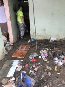 Voluntarios usan una excavadora para limpiar una casa abandonada que, debido a su proximidad con otras casas, se había convertido en la fuente de la infestación de mosquitos y ratas para el resto del vecindario.