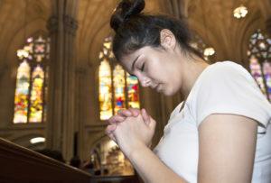 Joven rezando en una iglesia.