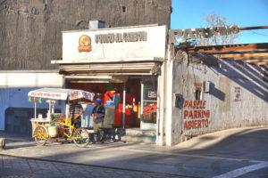 Un vendedor ambulante vende elotes afuera de un restaurante en Juárez.