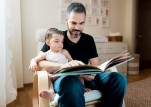 Un padre sentado en la silla con un bebé leyendo un libro. Hay pocos programas de educación disponibles para ayudar a papás.