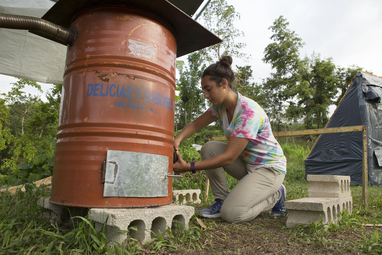 Michelle Farhat, estudiante de maestría en la Escuela de Medio Ambiente y Sostenibilidad de la Universidad de Michigan (SEAS) revisa el gasificador que ella y su equipo construyeron en la Universidad de Puerto Rico Utuado. Crédito de foto: Levi Stroud