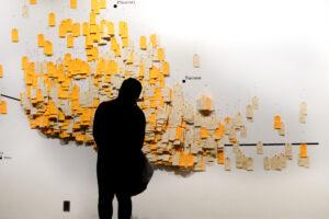 """Una persona mira """"Hostile Terrain 94"""" durante una una exposición preliminar realizada en el Phillips Museum of Art de Franklin & Marshall College en Lancaster, Pensilvania, en enero de 2019. Crédito: Daniel López, cortesía del Undocumented Migration Project."""
