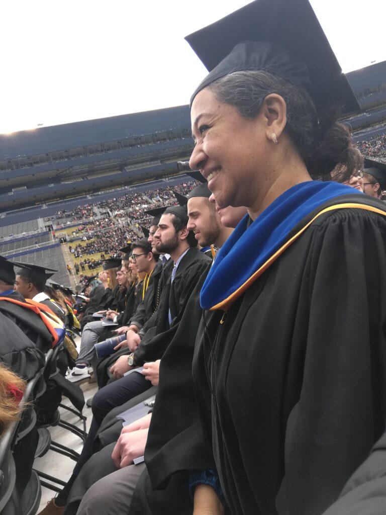 """María Militzer, ahora una investigadora posdoctoral en la Escuela de Salud Pública de la Universidad de Michigan, recibe su doctorado durante la ceremonia de graduación de 2019 en el estadio de Universidad de Michigan conocido como """"the Big House"""". Foto cortesía: María Militzer."""