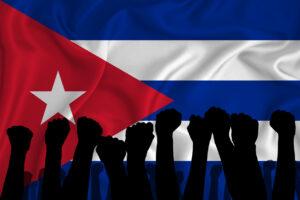 Silueta de brazos levantados y puños cerrados en el fondo de la bandera de cuba. El concepto de poder, conflicto. Crédito: Istockphoto